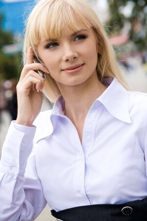 Portrait of beautiful woman looking at camera while speaking on her cell photo