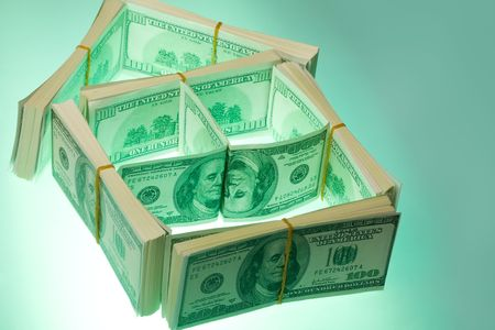 landlord: Image of house structure made of hundred-dollar banknotes on green lit background Stock Photo