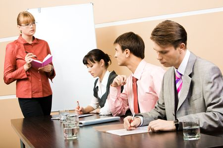 Image of smart teacher looking at businessman and speaking to him in workshop photo