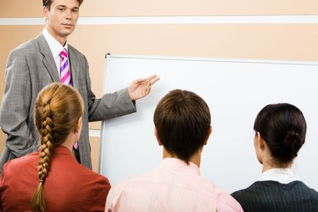 Image of serious businessman pointing at whiteboard with three partners listening to him photo