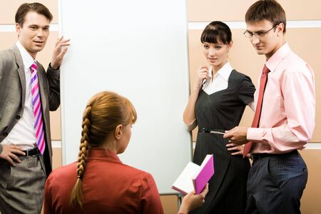 Portrait of young specialists looking at their leader with whiteboard at background Stock Photo - 3716844
