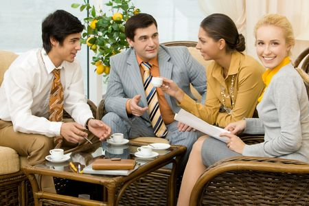 people communicating: Portrait of successful people communicating in office around table and having tea