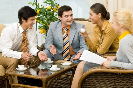 Photo of friendly company of businesspeople sitting in comfortable chairs and chatting with each other photo