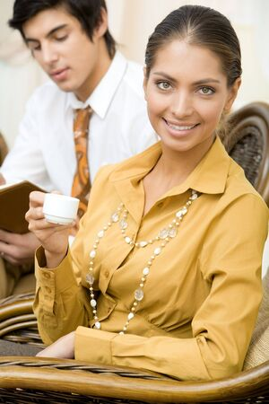 Portrait of elegant business lady with cup of coffee in hands on background of handsome man photo