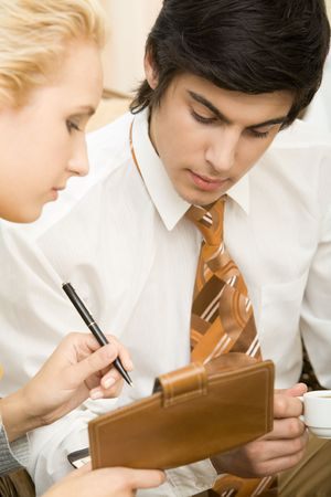 Close-up of young man looking at notepad in female's hand photo