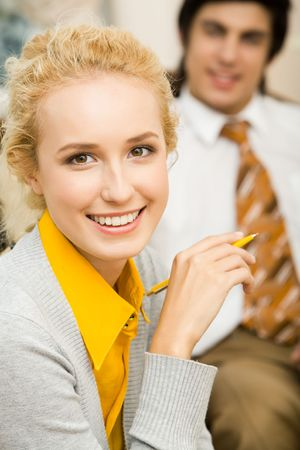 Portrait of blond woman looking at camera with smile on background of man photo