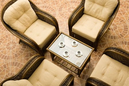 arm chairs: Above view of glass table surrounded by four brown arm chairs  Stock Photo