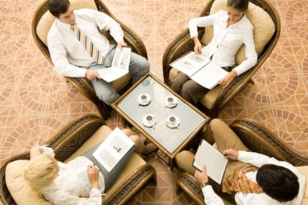 View from above of business people in armchairs reading documents photo