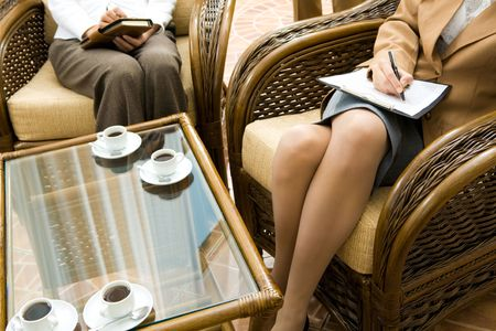 Creative image of two women sitting in armchairs with table near by photo
