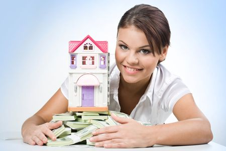 immovable: Portrait of beautiful woman touching heap of money with toy house on its top