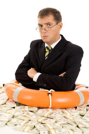 sulky: Portrait of sulky man inside lifebuoy and dollars around Stock Photo