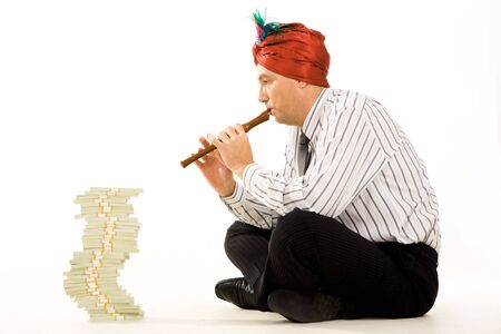 Creative photo of businessman wearing turban and playing the flute with stack of money in front of him photo