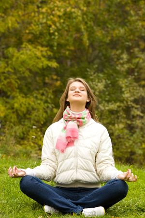 Portrait of pretty woman doing yoga exercise in the park  photo
