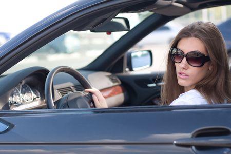 Portret van elegante moderne vrouw zit in een luxe auto Stockfoto