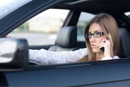 learner: Image of busy woman calling on cellular phone while sitting in her car Stock Photo