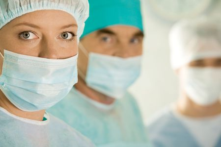 physicals: Portrait of female surgeon wearing protective mask on background of her colleagues