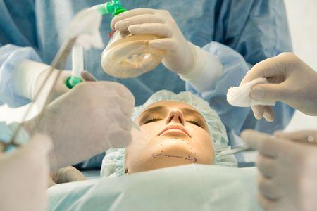 zuurstof: Foto van jonge vrouwelijke patiënt liggen met gesloten ogen voor samenwerking met de handen van artsen over haar