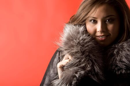 Portrait of beautiful Asian girl wearing fashionable fur coat and looking at camera Stock Photo - 3725038