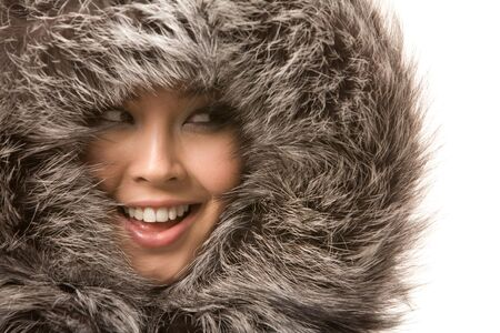 aside: Beautiful young girl in fur clothing laughing while looking aside over white background