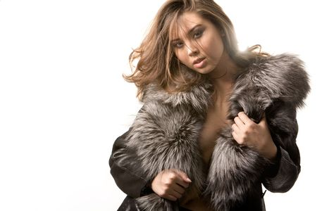Portrait of sexy female in fashionable coat posing during photoshoot photo
