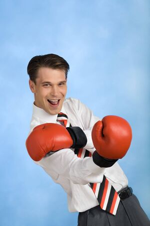 Portrait of Happy businessman wearing red boxing gloves and looking at camera photo