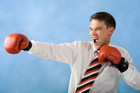 Portrait of shouting businessman stretching his gloved hand while doing boxing photo