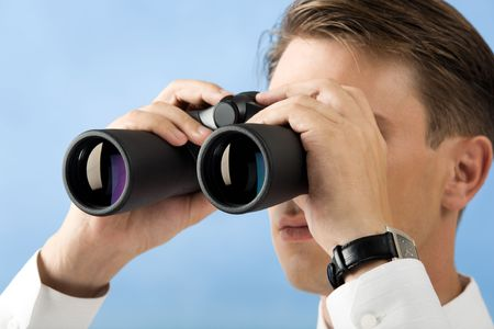 Close-up of man looking through binoculars on light blue background photo