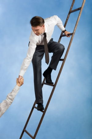 helping people: Conceptual image of successful businessman standing on ladder and giving hand to his partner
