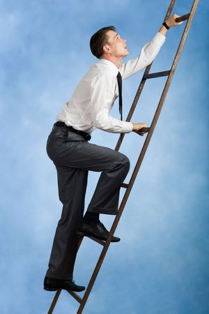 Photo of young businessman climbing upwards upon ladder