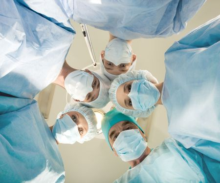 View of doctors by patient after operation on background of lamp and ceiling Stock Photo - 3725027