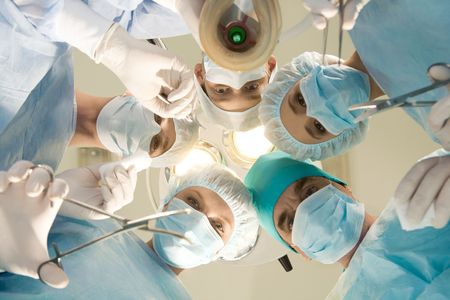 Below view of surgeons holding medical instruments in hands and looking at patient Stock Photo - 4111918
