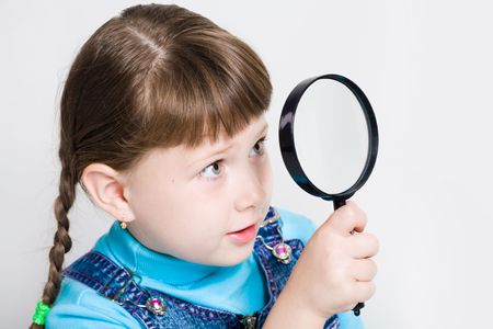 schoolkid search: Close-up of small girl holding looking glass in hand and watching through it