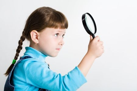 Image of cute girl with lens in hand looking slightly upwards through it photo