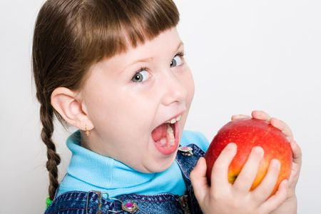 widely: Cute girl looking aside with widely open mouth ready to eat red juicy apple