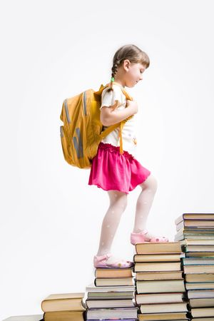 Image of schoolgirl with backpack stepping upon stairs made of books