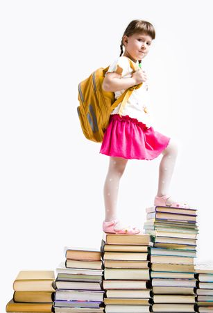 Image of serious schoolgirl standing on book stairs and looking at camera