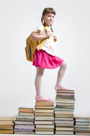 Image of clever girl with backpack standing on heap of books photo