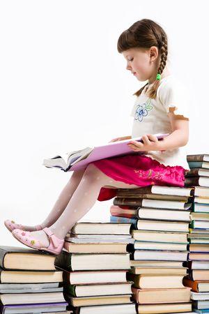 diligente: Perfil del alumno diligente sentado en la pila de libros y la lectura uno de ellos
