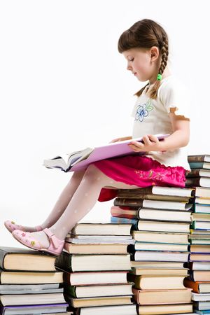 diligent: Profile of diligent pupil sitting on pile of books and reading one of them