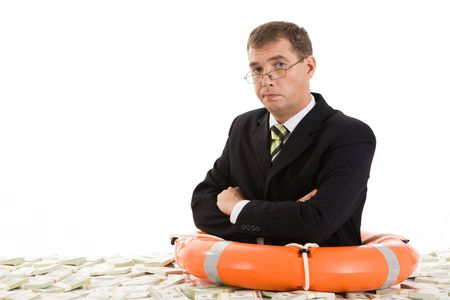 Image of frustrated man with life buoy surrounded by dollars photo