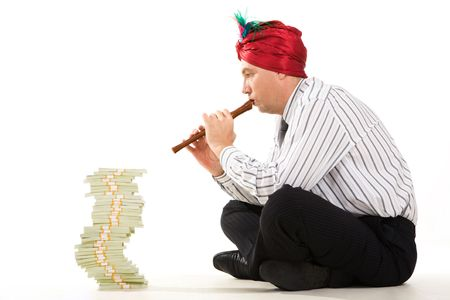 Image of entrepreneur playing the pipe with high stack of dollar bills in front photo