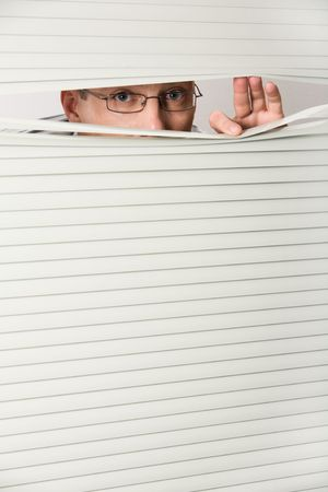 peeping: Photo of businessman standing behind venetian blind and peeping  Stock Photo