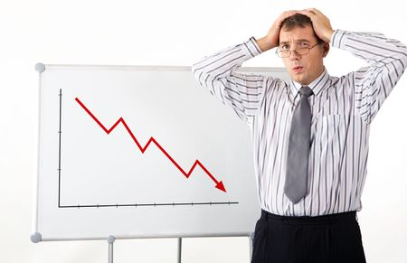 Portrait of frustrated man touching his head with whiteboard representing decreasing graph on it photo