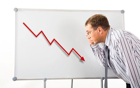 Image of serious man inclining to whiteboard and looking at recession graph on it photo