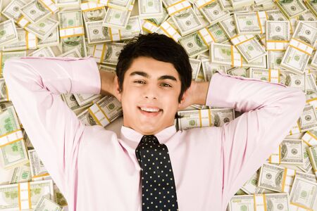 Image of happy businessman lying on heap of dollars and smiling photo