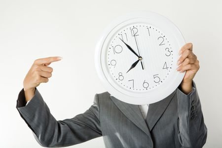 Image of female�s hands holding clock in front of face and pointing at it photo