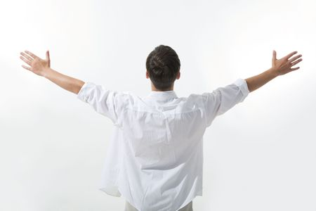 Rear view of man wearing white shirt and stretching his arms Stock Photo