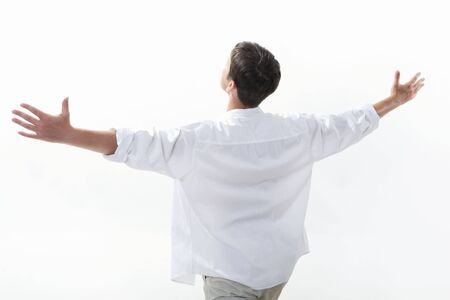 View from aside of happy young man raising his arms enjoying life photo