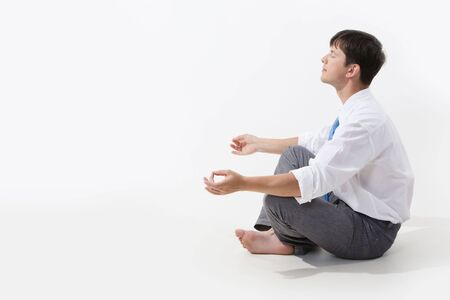 Meditating man sitting in pose of lotus in profile over white background Stock Photo