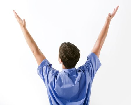 hands raised: Rear view of man in blue shirt keeping his arms raised over white background Stock Photo